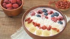 Smoothie bowl topped with raspberries, banana, coconut and goji berries Stock Footage