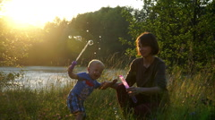 Cute young mother with a small son run the soap bubbles. Slow motion Stock Footage
