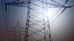 Power pylons and wires against cloudless sky, dolly shot. 4K seamless loopable Stock Footage