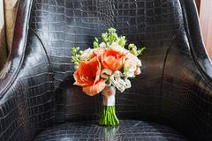 Wedding bouquet on leather chair. Bride's traditional symbolic accessory. Flo Stock Photos