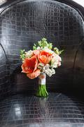Wedding bouquet on leather chair. Bride's traditional symbolic accessory. Flo - stock photo