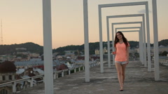 Sexy brunette model in orange t-shirt and blue shorts walking and posing  Stock Footage