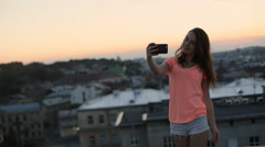 Beautiful woman in orange t-shirt and shorts taking selfie using phone at sunset Stock Footage