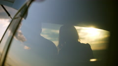 Silhouettes of young couple sitting in car trunk in field at sunset Stock Footage