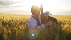 Young man playing pandora in wheat field at sunset Stock Footage