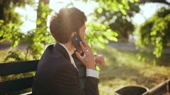 Young successful businessman speaking on phone on bench in morning park Stock Footage