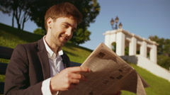 Young successful businessman reading magazine on bench in morning park Stock Footage