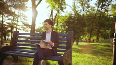 Young successful businessman with magazine sitting on bench in morning park Stock Footage