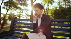 Young successful businessman speaking on phone on bench in morning park. Slow Stock Footage
