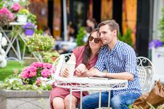 Restaurant tourists couple eating at outdoor cafe. Young woman enjoy time with Kuvituskuvat