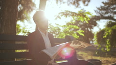 Young successful businessman reading magazine on bench in morning park. Slow Stock Footage