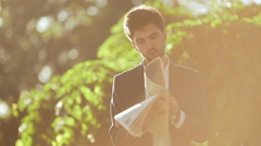 Young successful businessman reading magazine in morning park. Slow motion Stock Footage