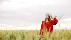 Young beautiful girl with foxy hair in red dress and hat with baloons walking in Stock Footage