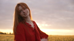 Young beautiful girl with foxy hair in red dress walking in field. Slow motion Stock Footage