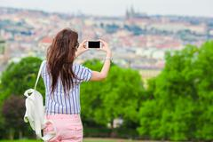 Young caucasian woman making photo of european old city by mobile phone from the - stock photo
