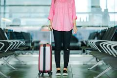 Closeup airplane passenger and pink baggage in an airport lounge waiting for Stock Photos