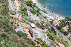 Aerial view Sicilian coast of Taormina with hotels and beach - stock photo