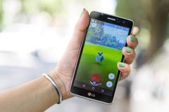 Pokemon Go game in a hand. Zubat Stock Photos