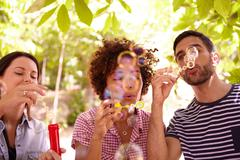 Three funloving friends blowing bubbles and smiling in the dappled afternoon  - stock photo