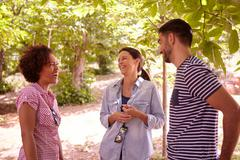 Three friends laughing at jokes in the dappled afternoon sunshine with some t Stock Photos