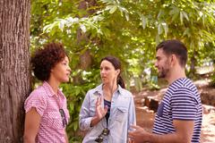 Two girl friends and a guy chatting in the dappled afternoon sunshine while o - stock photo