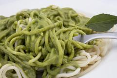 Italian pasta spaghetti with pesto sauce and basil leaf close-up. Stock Photos