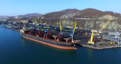 Aerial panoramic view of the cargo cranes, loading coal into the bulk cargo ship Stock Footage