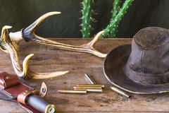 Hunting gun, deer antlers, knife, bullet and hat Stock Photos