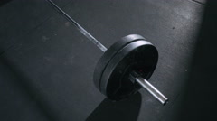Closeup of barbell lying on gym floor ready for deadlift Stock Footage