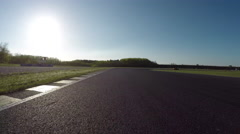 FPV LOW ANGLE: Racecar driving fast competing on racetrack on sunny day Stock Footage