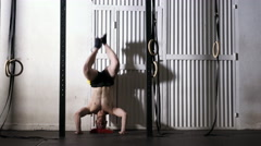 Handstand push-ups exercise - young athletic man doing gym workout Stock Footage