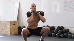 Kettlebell squat exercise - young man doing weights workout at gym Stock Footage