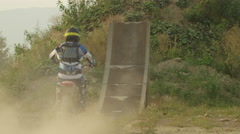 SLOW MOTION: Extreme pro motocross biker riding motorbike and jumping huge jump Stock Footage