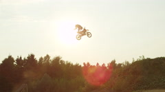 SLOW MOTION: Extreme pro motocross biker jumping superman trick over the sun Stock Footage