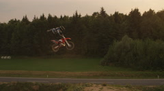 AERIAL SLOW MOTION: Extreme pro motocross biker jumping no footer big air Stock Footage