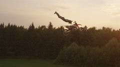 AERIAL SLOW MOTION: Pro motocross biker riding and jumping no hander superman Stock Footage