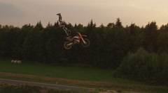 AERIAL SLOW MOTION: Extreme motocross biker jumping no footer trick at sunset Stock Footage