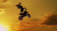 SLOW MOTION CLOSEUP: Extreme motocross biker jumping freestyle trick at sunset - stock footage