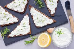 Pumpernickel bread with feta, cream cheese, rosemary, lemon, garlic dip - stock photo