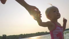 Slow motion baby girl walking on the beach, holding his mother's hand at sunset Stock Footage