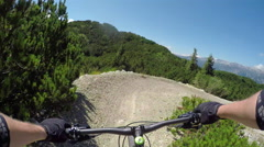 FPV: Extreme biker riding downhill along the rocky flow track in bike park Stock Footage