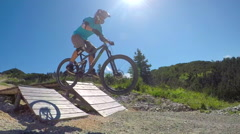 SLOW MOTION: Downhill biker jumping over wooden trail jump in mountain bike park Stock Footage