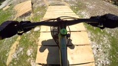 FPV: Beginner biker riding downhill along the easy wooden trail in bike park Stock Footage
