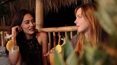 Caucasian and asian women chatting in a bar with drinks, laughing Arkistovideo
