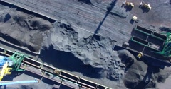 Aerial view of a process of coal loading into cargo waggons by cargo cranes. Stock Footage