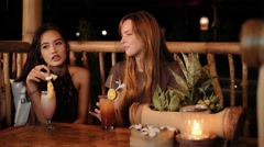 Caucasian and asian women chatting in a bar with drinks, smiling Arkistovideo