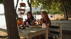 Сaucasian and asian women having breakfast on beach in Pemuteran bay Stock Footage