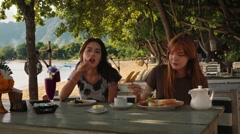 Сaucasian and asian women having breakfast on beach in Pemuteran bay, smiling Stock Footage