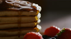 Maple syrup being poured over warm stacked pancakes with fruit, in slow motion Stock Footage