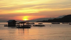 Sunrise in Pemuteran bay, Bali - hut and boats on water Stock Footage